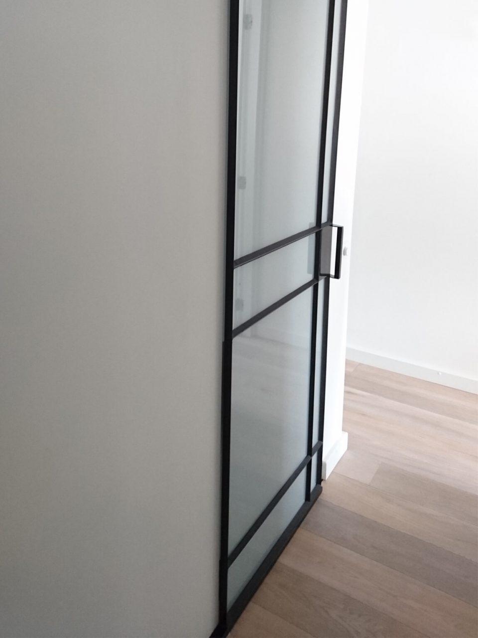 stalen schuifdeur met melkglas in luxe badkamer gerealiseerd door StalenDeurenHuys